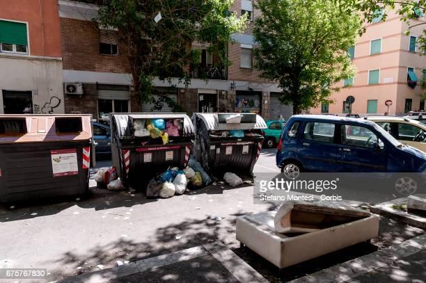 Wastes bins overflow and a sofa lies in the street in Torpignattara neighborhood on May 1 2017 in Rome Italy
