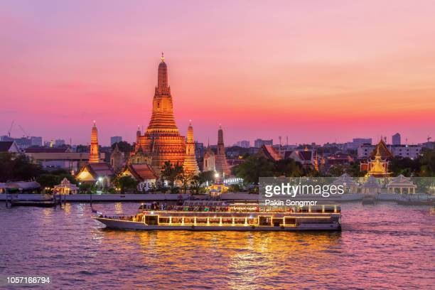 wat arun and cruise ship in twilight time - bangkok stock photos and pictures