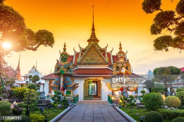 wat arun is a buddhist temple in bangkok yai district of bangkok, thailand. wat arun is one of famous landmark temple at sunset in bangkok thailand. giants front of the church at wat arun. - tempel stock-fotos und bilder