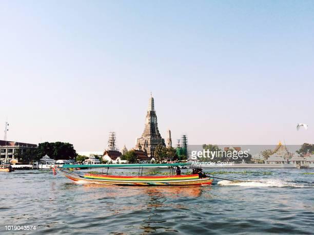 Wat Arun temple and a boat on Chao Phraya River, Bangkok, Thailand