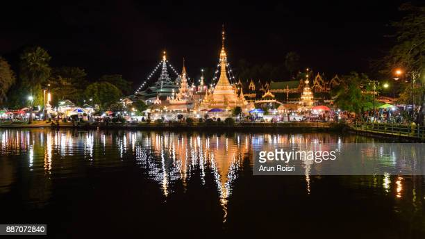 Wat Jong Klang temple reflected in the Nong Jong Kham pond in center of Mae Hong Son City, Northern Thailand