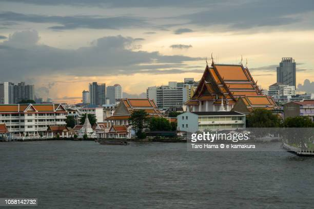 Wat Kalayanamit Woramahawihan Buddhist temple and Chao Phraya River in Bangkok in the sunset