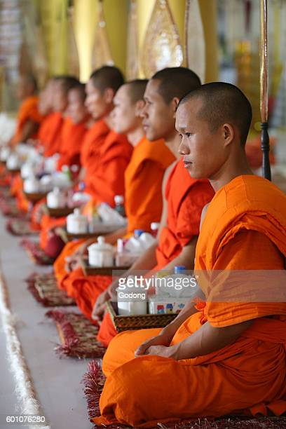 Wat Ong Teu buddhist temple Seated Buddhist monks chanting and reading prayers at a ceremony Vientiane Laos