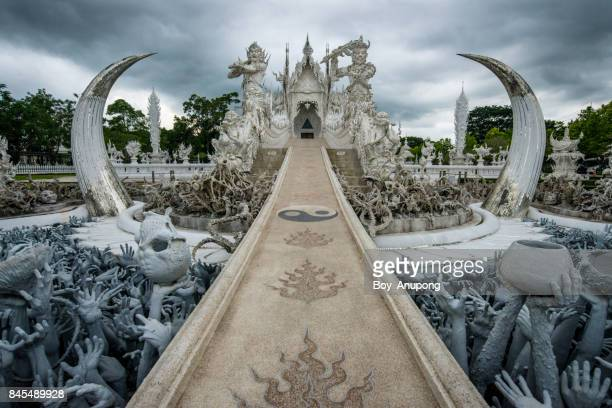 wat rong khun (white temple) in chiang rai province of thailand in the cloudy day. - hell stock pictures, royalty-free photos & images