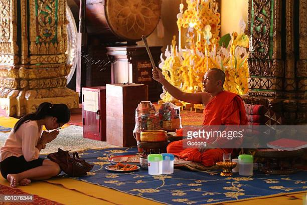 Wat Si Muang buddhist temple Buddhist ceremony Monk sprinkling holy water Vientiane Laos
