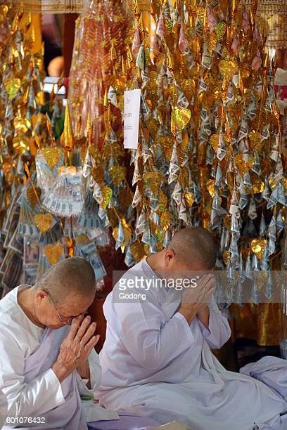 Wat Si Muang buddhist temple Buddhist ceremony Worshipers praying Vientiane Laos