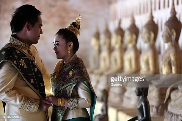Wat Sisaket buddhist temple. Wedding couple wearing traditional Lao costumes. Vientiane, Laos.
