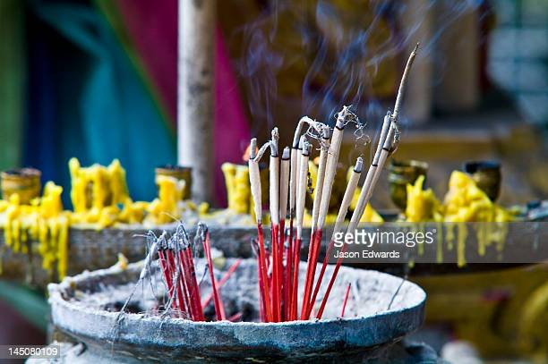 Incense and candles burning in a small temple in a riverside market.