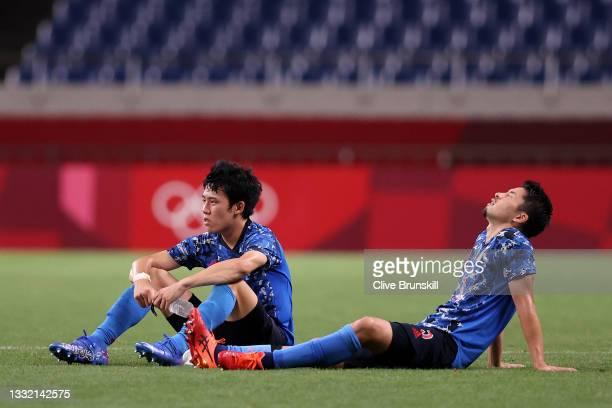 Wataru Endo and Maya Yoshida of Team Japan look dejected following defeat in the Men's Football Semi-final match between Japan and Spain on day...