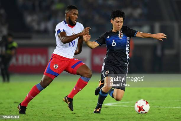 Wataru Endo of Japan and Duckens Nazon of Haiti compete for the ball during the international friendly match between Japan and Haiti at Nissan...