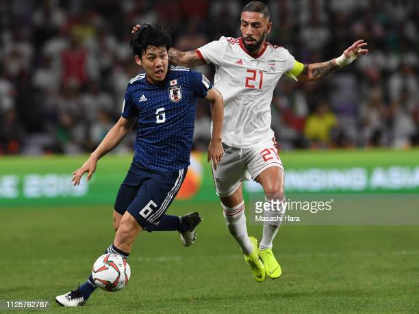 Wataru Endo of Japan and Seyed Ashkan Dejagah of Iran compete for the ball during the AFC Asian Cup semi final match between Iran and Japan at Hazza...
