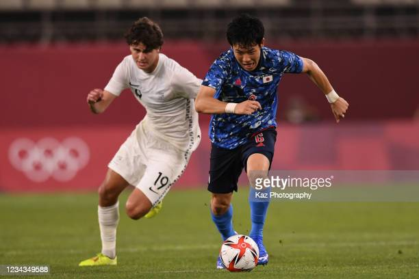 Wataru Endo of Japan dribbles the ball under the pressure from Matthew Garbett of New Zealand during the Men's Quarter Final match on day eight of...