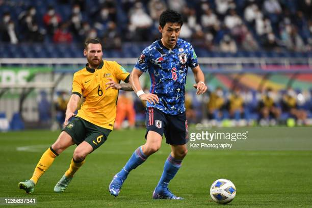 Wataru Endo of Japan keeps the ball under the pressure from Martin Boyle of Australia during the FIFA World Cup Asian qualifier final round Group B...