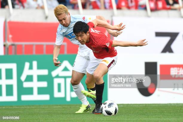 Wataru Endo of Urawa Red Diamonds and Akito Fukumori of Consadole Sapporo compete for the ball during the JLeague J1 match between Urawa Red Diamonds...