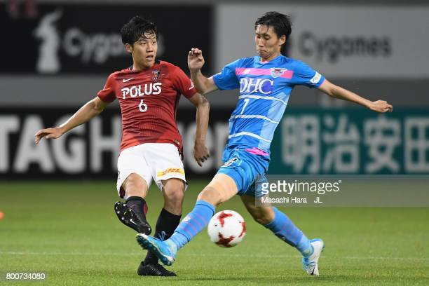 Wataru Endo of Urawa Red Diamonds and Daichi Kamada of Sagan Tosu compete for the ball during the JLeague J1 match between Sagan Tosu and Urawa Red...