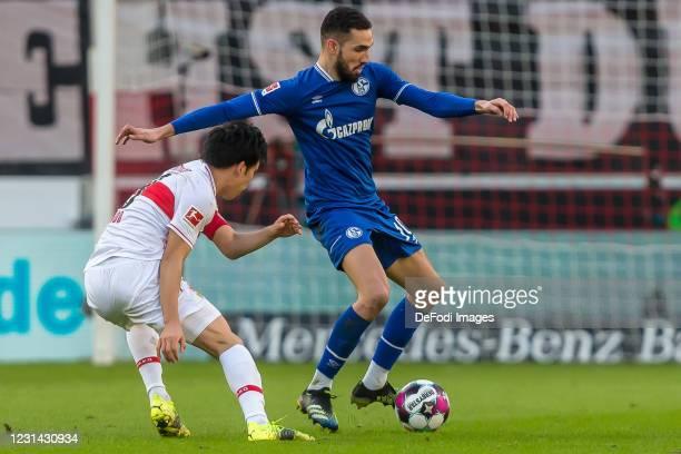 Wataru Endo of VfB Stuttgart and Nabil Bentaleb of FC Schalke 04 battle for the ball during the Bundesliga match between VfB Stuttgart and FC Schalke...
