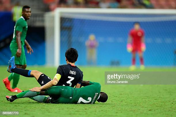 Wataru Endo player of Japan goes to ground after a challenge by Muenfuh Sincere player of Nigeria during 2016 Summer Olympics match between Japan and...