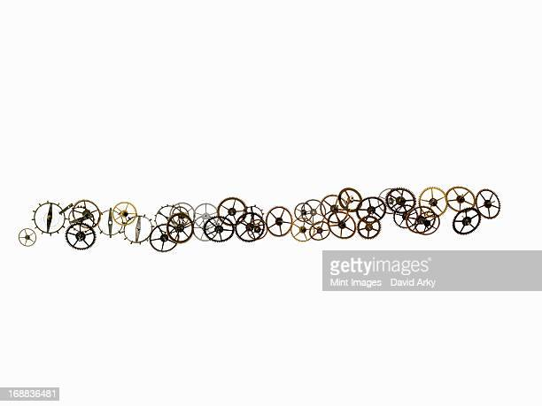 Watch gears, small precision made cog wheels with spokes and fine teeth or notches around the edge. Arranged in a irregular line.