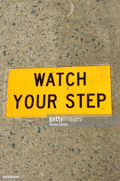 Watch Your Step sign on a concrete footpath