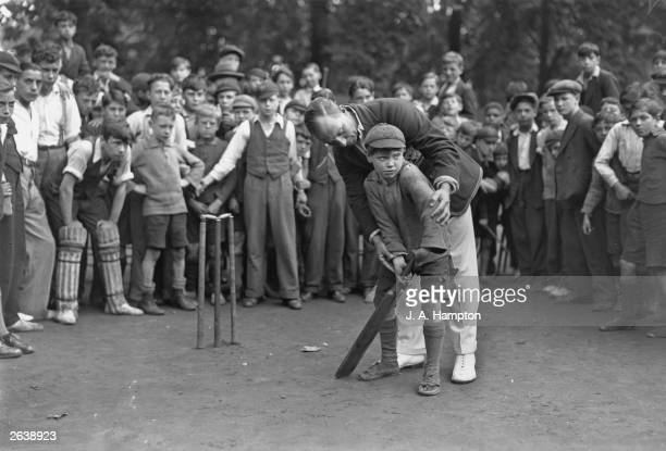 Watched by a crowd of boys England and Surrey batsman Andrew Sandham teaches a young boy the correct way to hold a cricket bat during a visit to the...