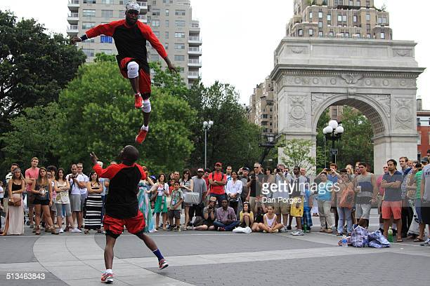 Watched by a crowd of onlookers a pair of street acrobats perform in Greenwich Village's Washington Square Park New York New York July 13 2013