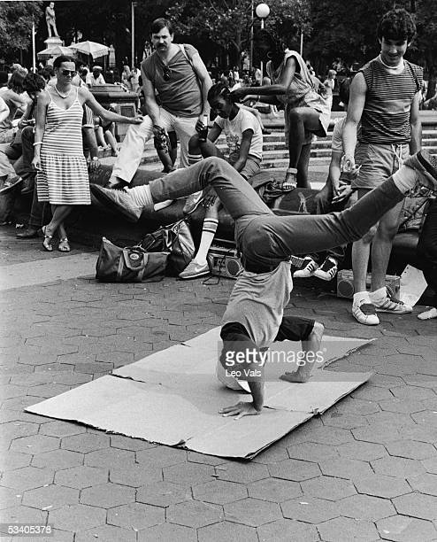 Watched by a group of spectators a young man breakdances in Washington Square Park New York New York early 1980s