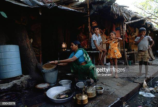 Watched by a group of young children a woman washes dishes in a bucket of water at a humble home on the sidewalk in Bombay India A little girl has a...