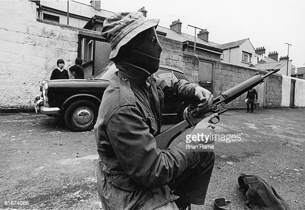 Watched by a pair of young boys and a pedestrian a masked IRA mean slides back the bolt of his suna s he kneels in a street Derry Northern Ireland...
