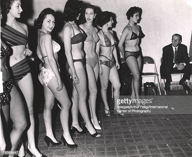 Watched by a seated man on a folding chair a group of woman in bikinis and high heels wait in line at a beauty contest 1940s or 1950s In the center...