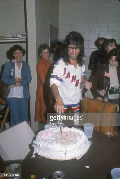 Watched by admirers and journalists American musician Alice Cooper cuts a cake backstage during his 'Welcome to My Nightmare' tour at Madison Square...