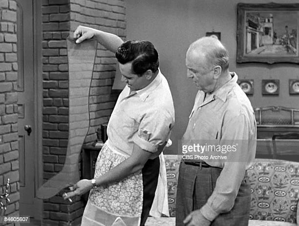 Watched by American actor William Frawley , Cuban-born American actor and musician Desi Arnaz holds up a woman's stocking, a cigarette in one hand,...