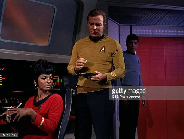 Watched by American actress Nichelle Nichols , Canadian actor William Shatner holds a plate on the bridge of the USS Enterprise in a scene from 'The...