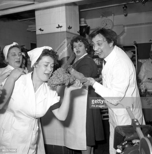 Watched by comedienne Hattie Jaques Liverpudlian comedian Kenn Dodd offers a female employee a taste of a giant Christmas pudding mixture he and...