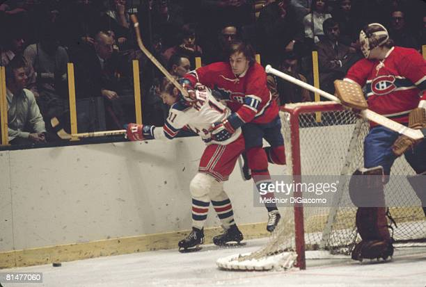 Watched by his team's goalie Canadian ice hockey player Ken Dryden Marc Tardif of the Montreal Canadiens leaps over the back of the New York Rangers'...