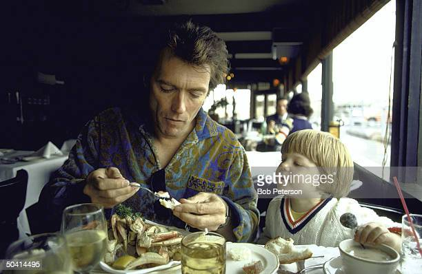 Watched by his threeyearold son Kyle American actor Clint Eastwood eats a crab in a Fisherman's Wharf restuarant San Francisco California 1971