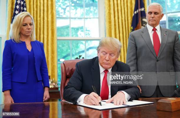 Watched by Homeland Security Secretary Kirstjen Nielsen and Vice President Mike Pence, US President Donald Trump signs an executive order on...