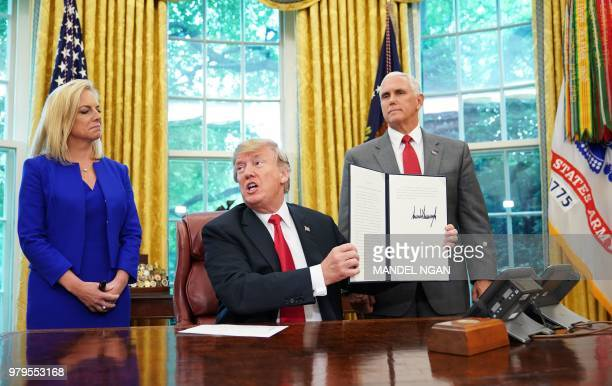 Watched by Homeland Security Secretary Kirstjen Nielsen and Vice President Mike Pence US President Donald Trump holds an executive order on...