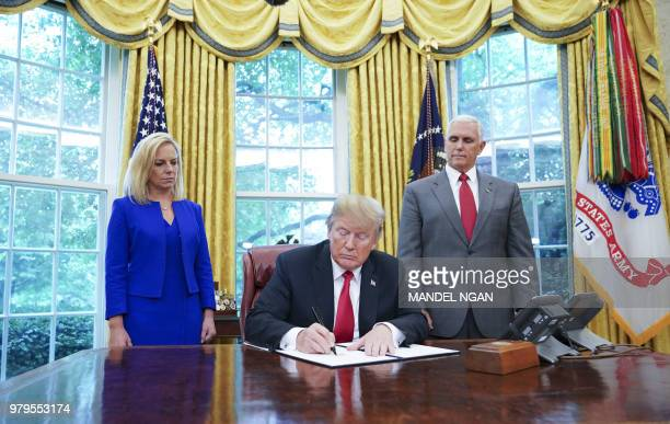 Watched by Homeland Security Secretary Kirstjen Nielsen and Vice President Mike Pence US President Donald Trump signs an executive order on...