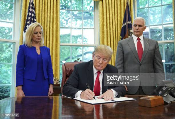 TOPSHOT Watched by Homeland Security Secretary Kirstjen Nielsen and Vice President Mike Pence US President Donald Trump signs an executive order on...