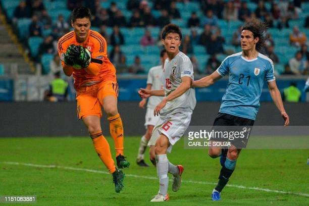 Watched by Japan's Takehiro Tomiyasu Japan's goalkeeper Eiji Kawashima catches the ball as Uruguay's Edinson Cavani follows the action during the...