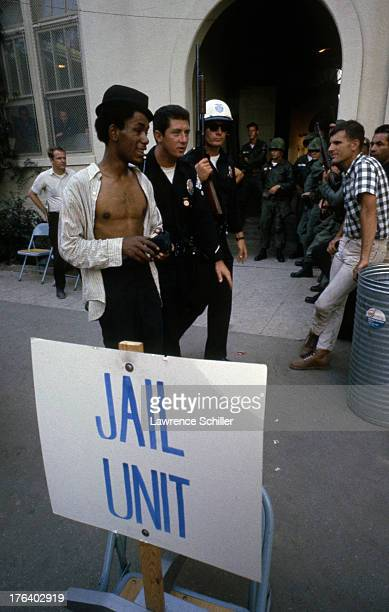 Watched by members of the National Guard Los Angeles Police Officers escort a young man past a sign that reads 'Jail Unit' in the Watts neighborhood...