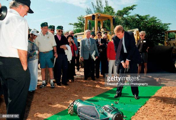 Watched by onlookers American real estate developer Donald Trump tees off during the Trump International Golf Club groundbreaking ceremony Palm Beach...