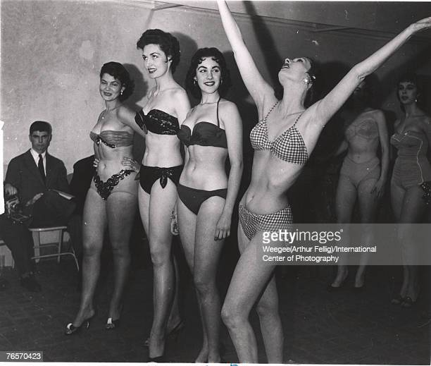 Watched by seated men on folding chairs a line of woman in bikinis and high heels wait at a beauty contest 1940s or 1950s In the forward line second...