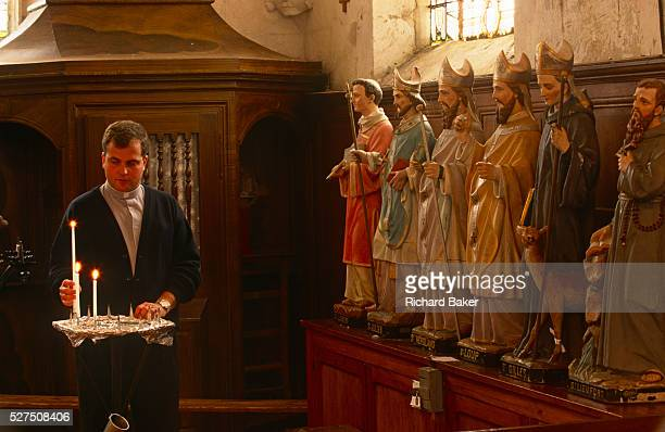 Watched by statues of saints, Father Phillipe Dubos a country priest lights candles before Sunday Mass in a local Catholic church in Iville St...