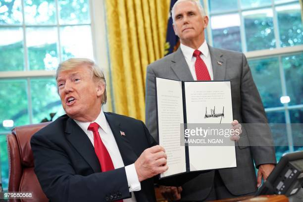TOPSHOT Watched by Vice President Mike Pence US President Donald Trump shows an executive order on immigration which he just signed in the Oval...