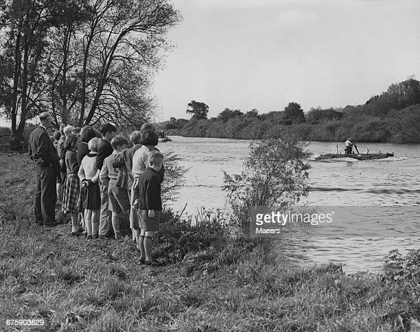 Watched from the riverbank by teachers and pupils from the local Riverside school Captain First Lieutenant Forbes stands on the deck of the Royal...