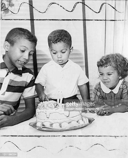 Watched with some concern by a boy and girl a young boy cuts a birthday cake with two candles 1960s The decorations on the cake have been drawn on...