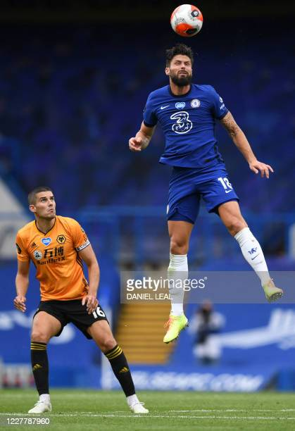 Watches as Chelsea's French striker Olivier Giroud jumps for the ball Wolverhampton Wanderers' English defender Conor Coadyduring the English Premier...