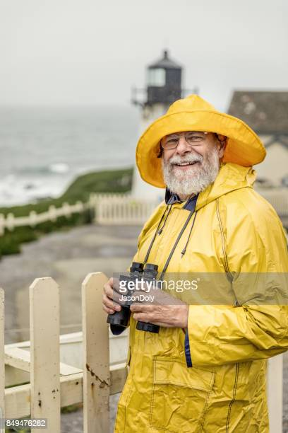 watchful eye of the lighthouse keeper - raincoat stock pictures, royalty-free photos & images