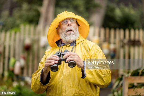watchful eye of the lighthouse keeper - raincoat stock photos and pictures